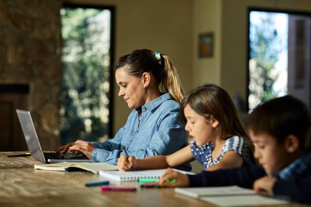 Mutter mit Laptop, während Kinder Hausaufgaben machen – Foto