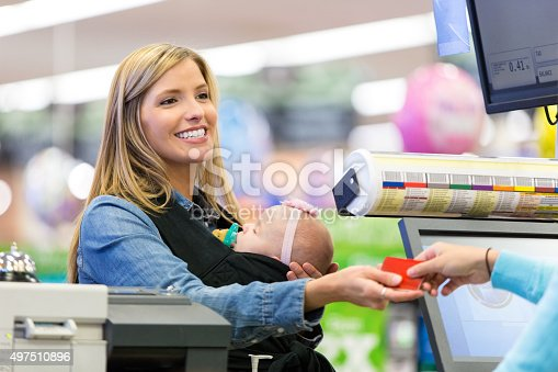 istock Mother using loyalty card or credit card in grocery store 497510896