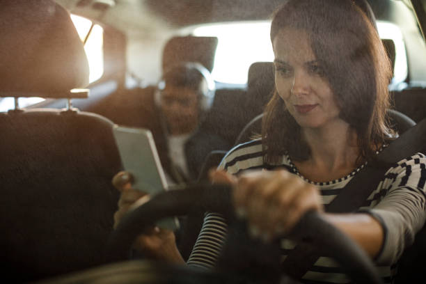 Mother using mobile phone while driving a car stock photo