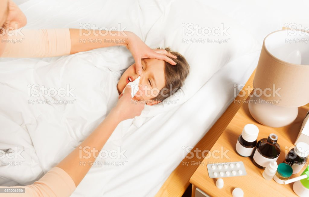 Mother using nasal spray to her sick kid son stock photo