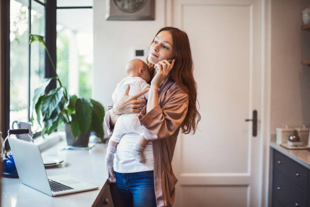 mother using phone while carrying baby in kitchen - busy stock photos and pictures