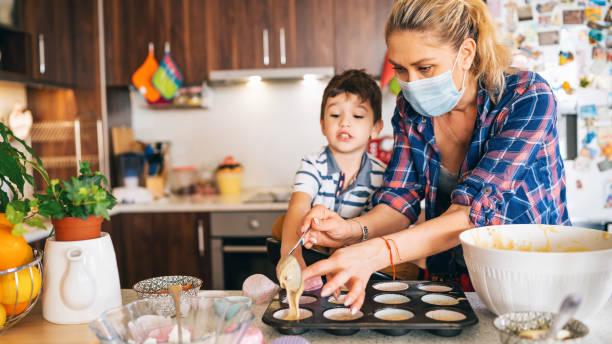 Mutter mit Schutzmaske machen leckere Cupcakes mit ihren Kindern Isolation zu Hause für Virus – Foto