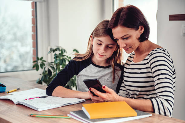 Mother using smart phone and helping daughter with homework Mother using smart phone and helping daughter with homework at the table in dining room by the window parent stock pictures, royalty-free photos & images