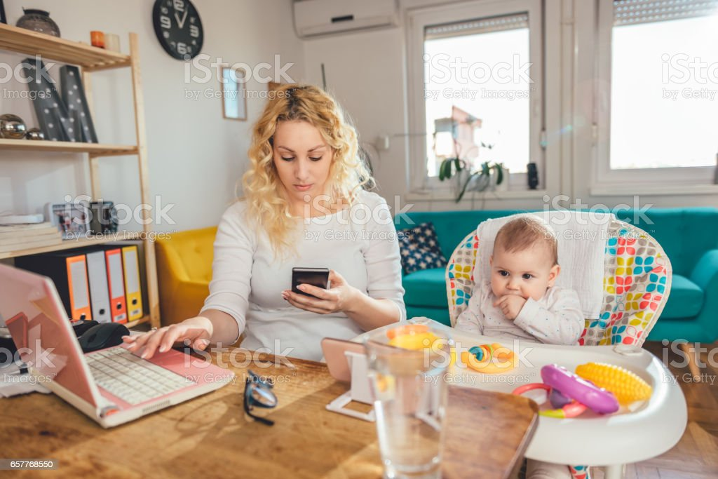 Mother using smart phone at home office with her baby stock photo