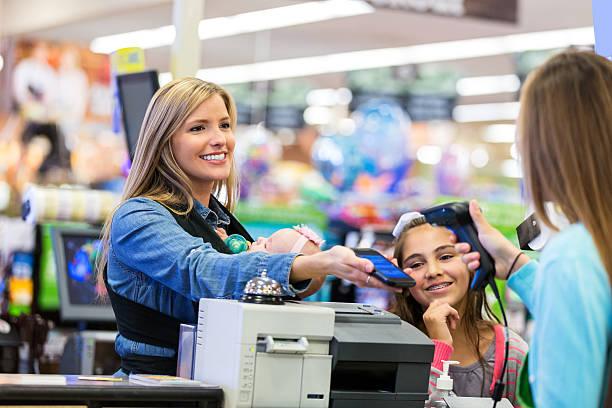 madre utilizzando smartphone per pagare acquisti effettuati in negozio - fedeltà foto e immagini stock