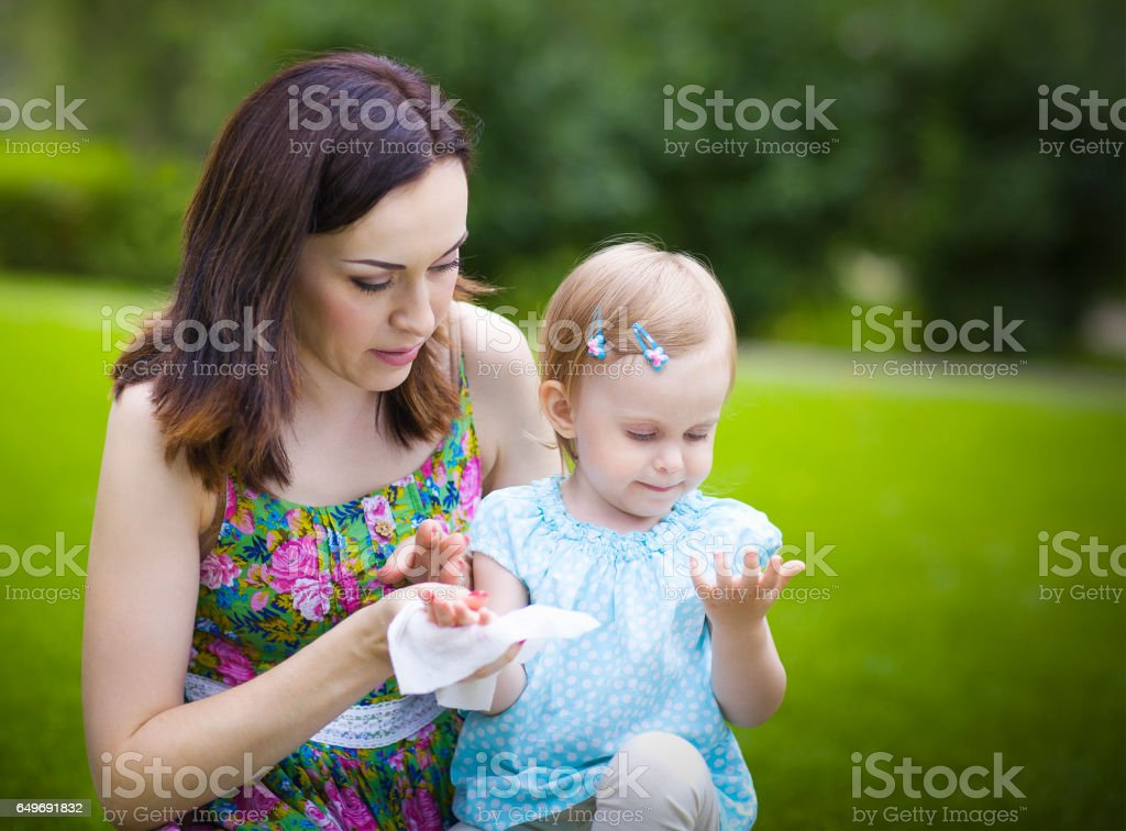 Mother using wet wipes for her daughter stock photo