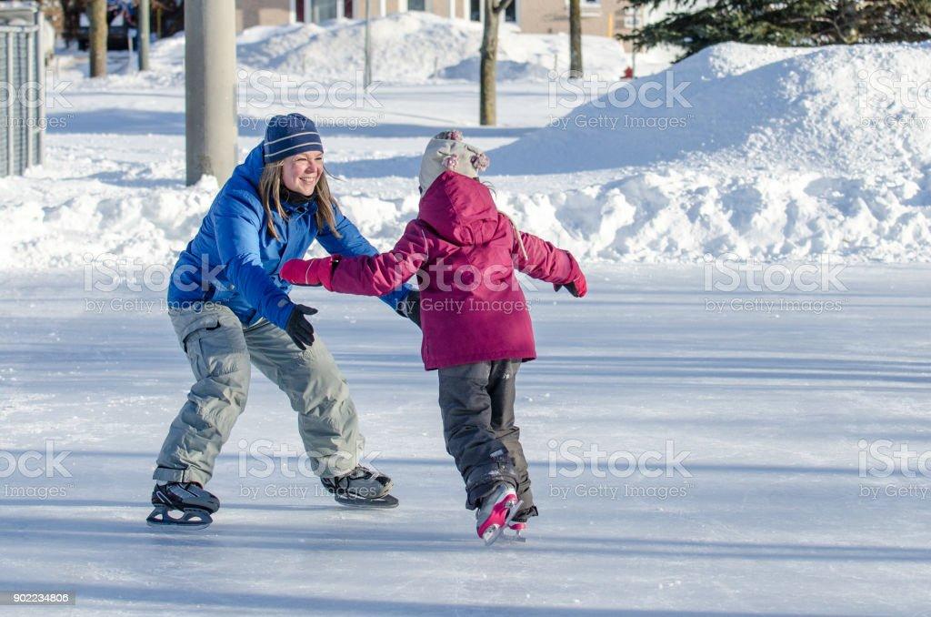 Mutter wartet mit Armen öffnete ihre Tochter zu helfen, ihre Eislaufen – Foto
