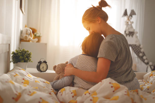 mother wakes her daughter in bed in  morning stock photo
