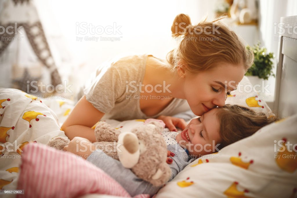 mother wakes her daughter in bed in  morning zbiór zdjęć royalty-free