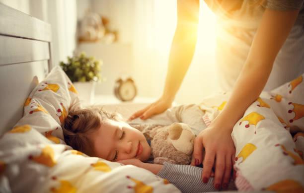 mutter aufwacht kind tochter mädchen schlafen, morgen - decke bettwäsche stock-fotos und bilder