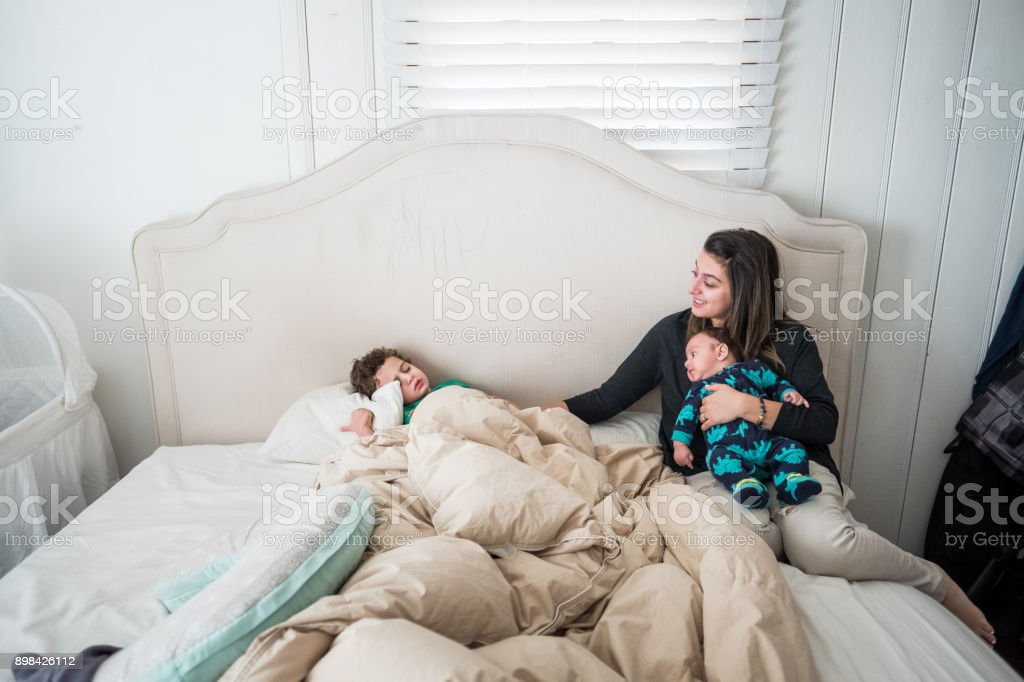Mother wakes up toddler son stock photo