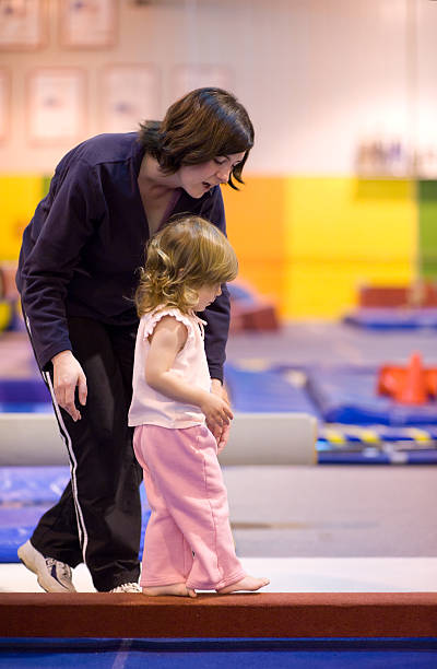 mother walking daughter down balance beam - balance beam stock photos and pictures