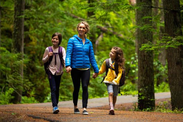 Mutter zu Fuß mit Mädchen im Wald in Richtung Schule – Foto