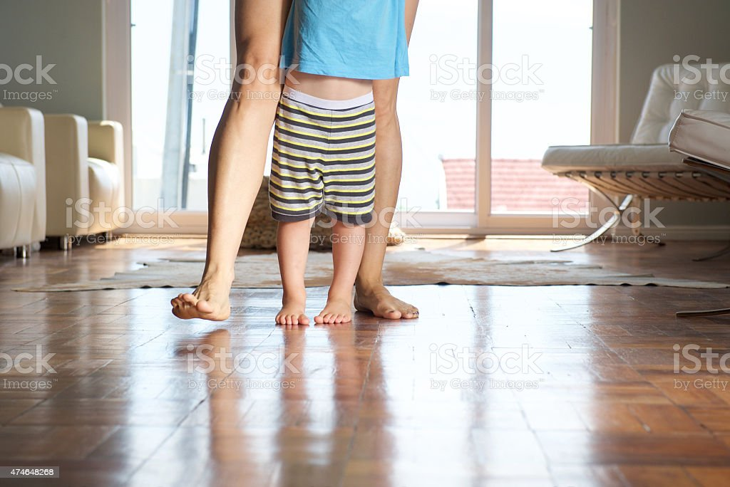 Mother walking with little boy at home stock photo