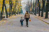 Young Caucasian mother walking with little son in park in autumn