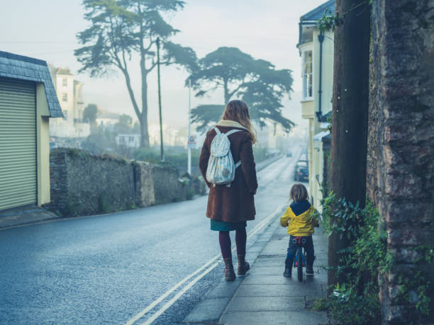 Mother walking with toddler in the street stock photo