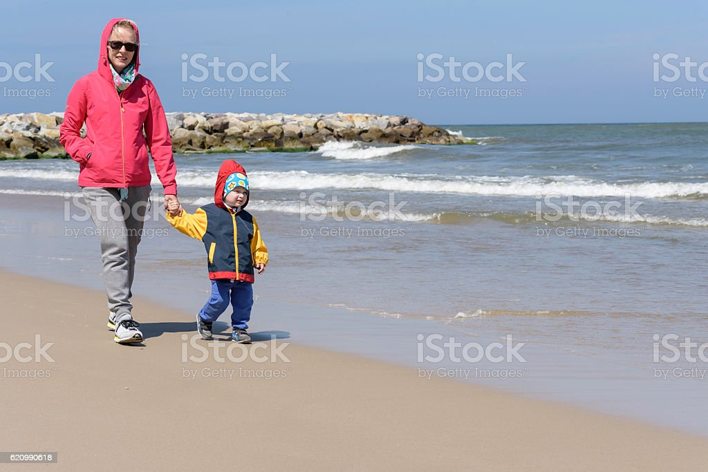 Mother walks on a beach with her litlle son foto royalty-free
