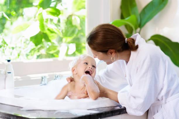 mamma tvätt baby i bubbelbad. vatten kul. - baby bathtub bildbanksfoton och bilder