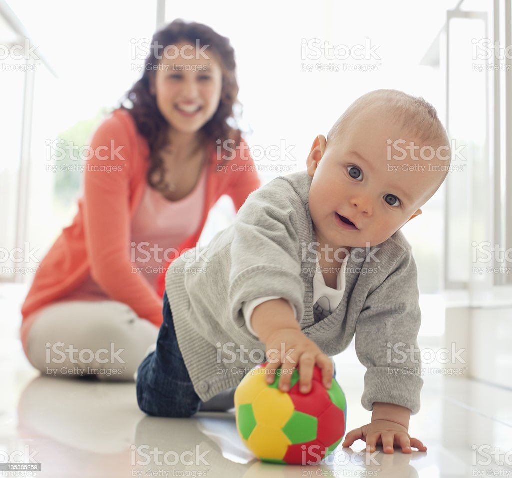 Mother watching baby playing with ball stock photo