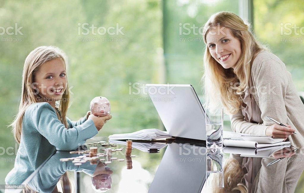Hija de madre viendo las monedas de alcancía - foto de stock