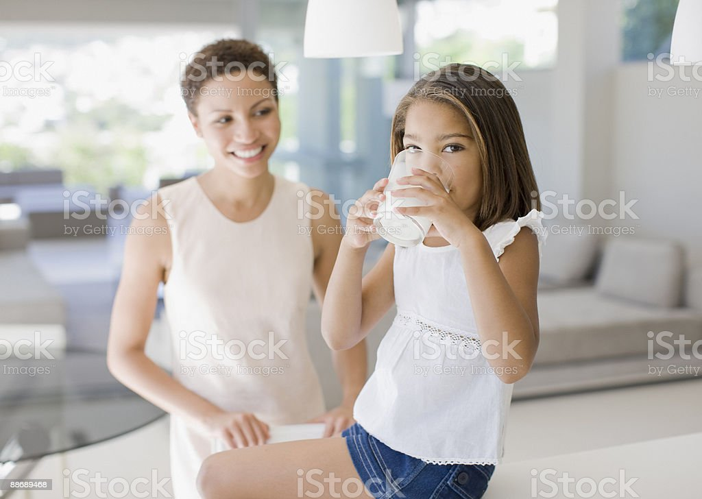 Madre e hija mirando bebida vaso de leche - foto de stock