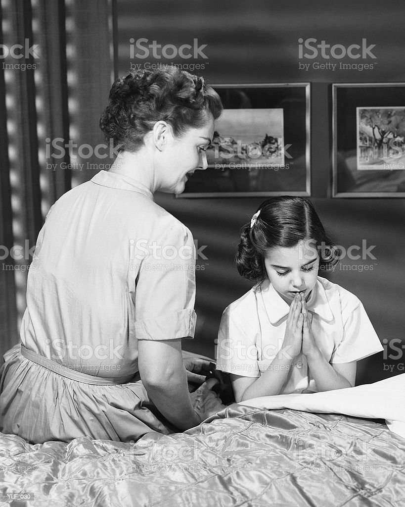 Mother watching daughter say bedtime prayers royalty-free stock photo