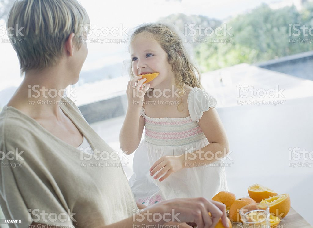 Mother watching girl eating orange royalty-free stock photo