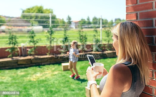 istock Mother watching mobile while son plays 866644616