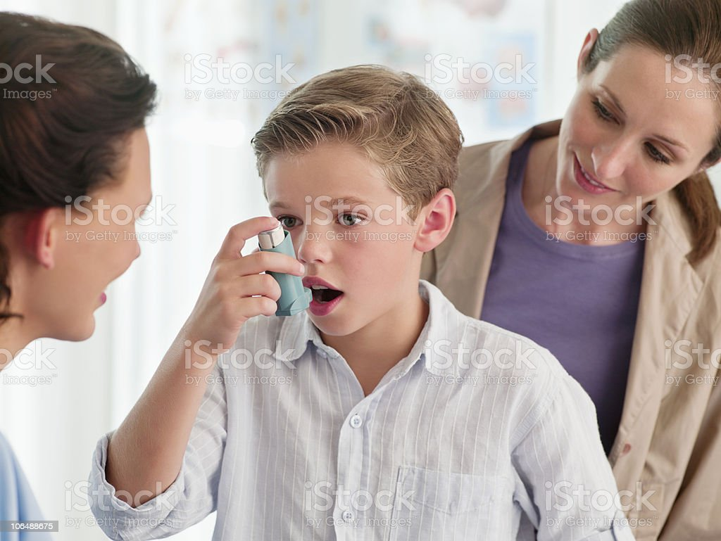 Mother watching nurse help boy (10-11) with an asthma inhaler stock photo