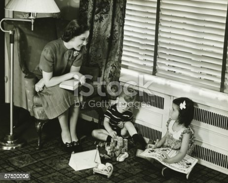 57520540 istock photo Mother watching over son and daughter (4-5) playing in living room, (B&W) 57520206