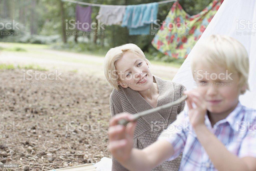 Mère en regardant son fils jouant au campement photo libre de droits