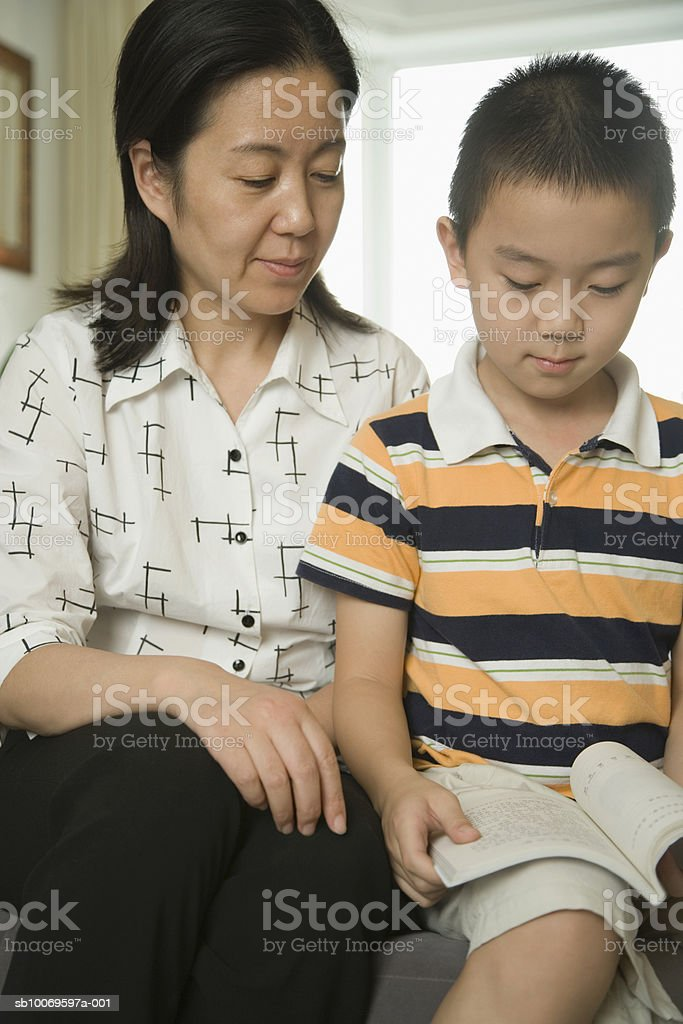 Mother watching son (8-9) reading book foto de stock royalty-free