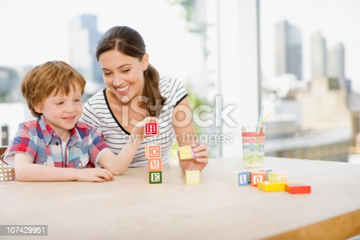istock Mother watching son stacking alphabet blocks and spelling home 107429951