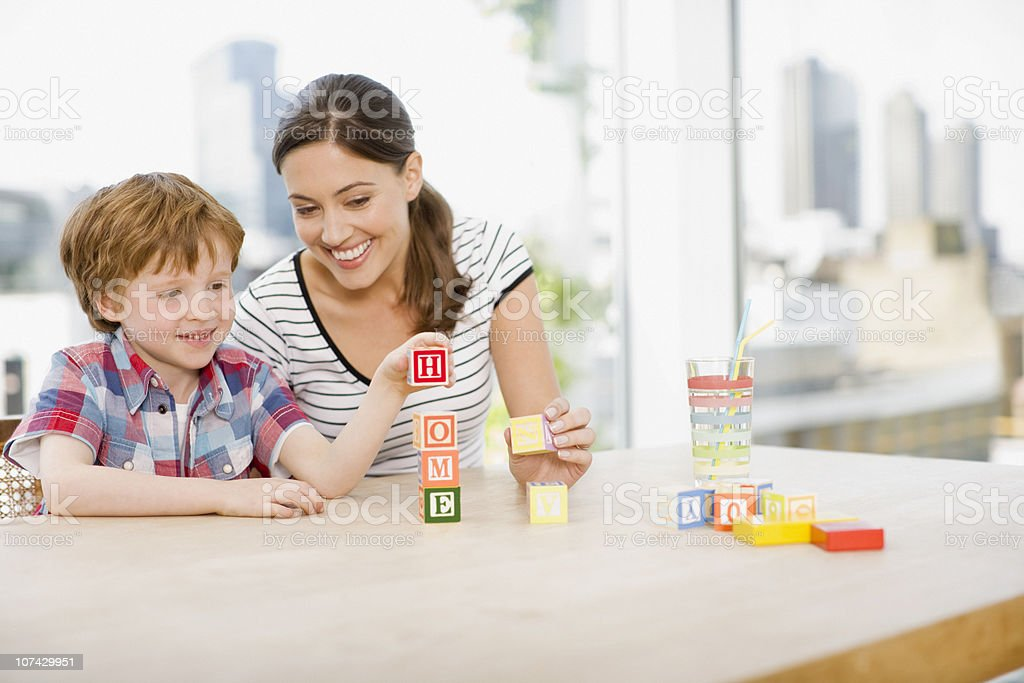 Mother watching son stacking alphabet blocks and spelling home stock photo