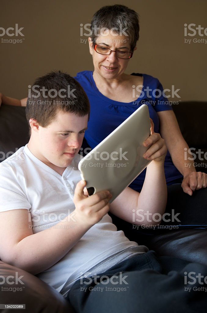 Mother watching teenager using a tablet to play video game stock photo