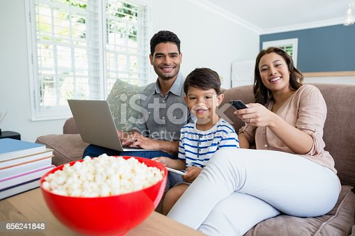1134439364 istock photo Mother watching television while father and son using laptop and digital tablet at home 656241848