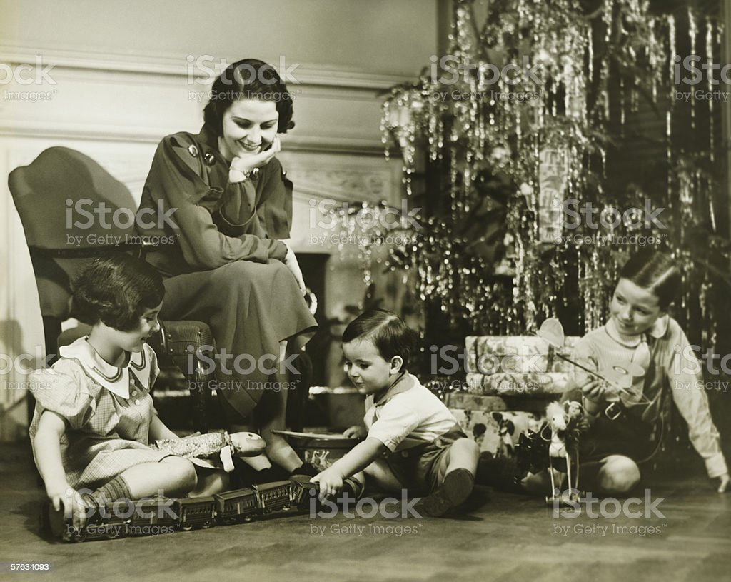 Mother watching three children playing by Christmas tree, (B&W) stock photo