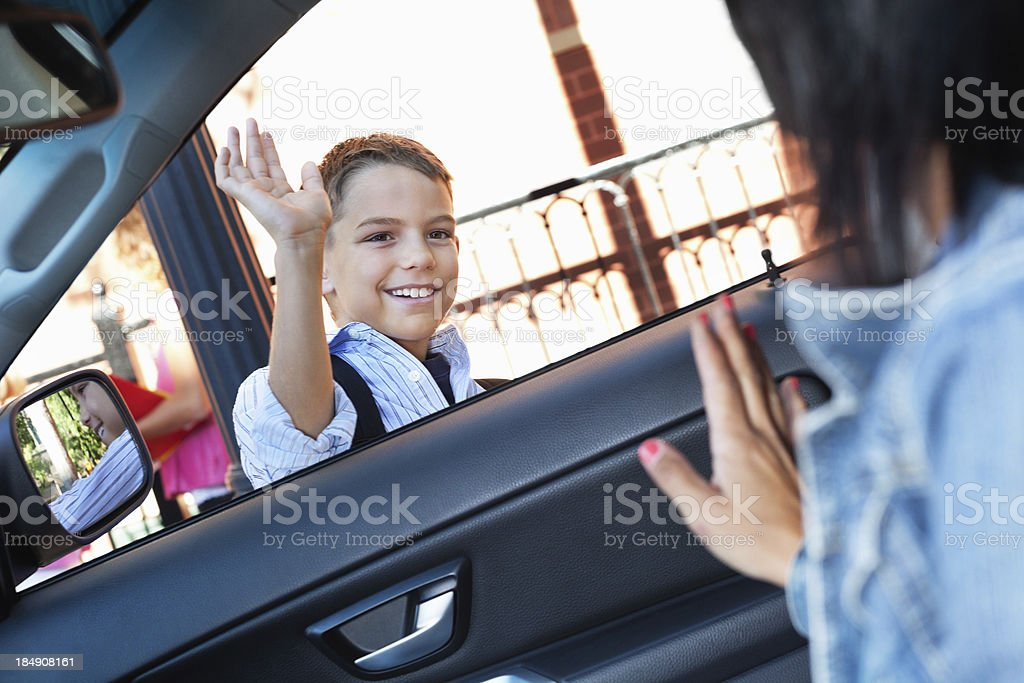 Mother waving to son as he's dropped off at school stock photo