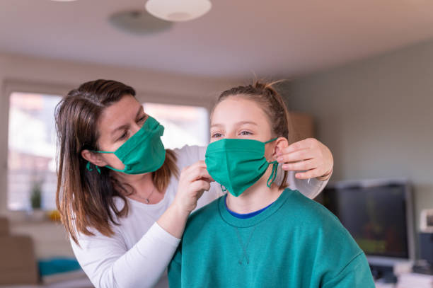 Mother wearing a homemade protective mask and putting one to her daughter Mother wearing a green homemade protective face mask and putting one to her daughter at home during the coronavirus Covid-19. pollution mask stock pictures, royalty-free photos & images
