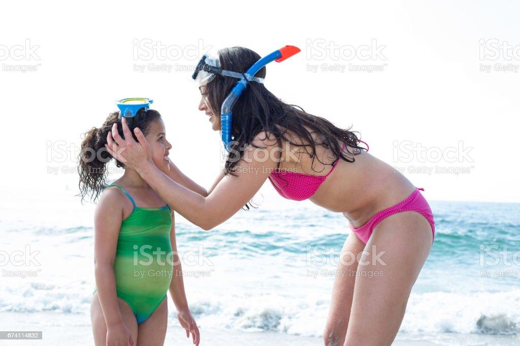 母親在海灘戴著潛水鏡的女兒 免版稅 stock photo