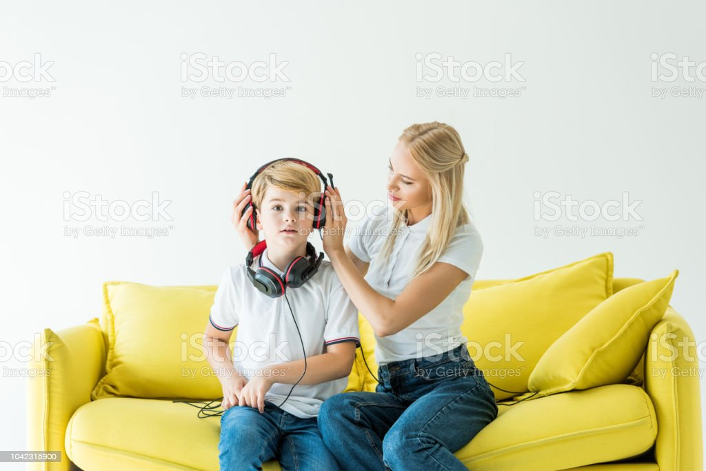 mother wearing headphones on son on yellow sofa isolated on white stock photo