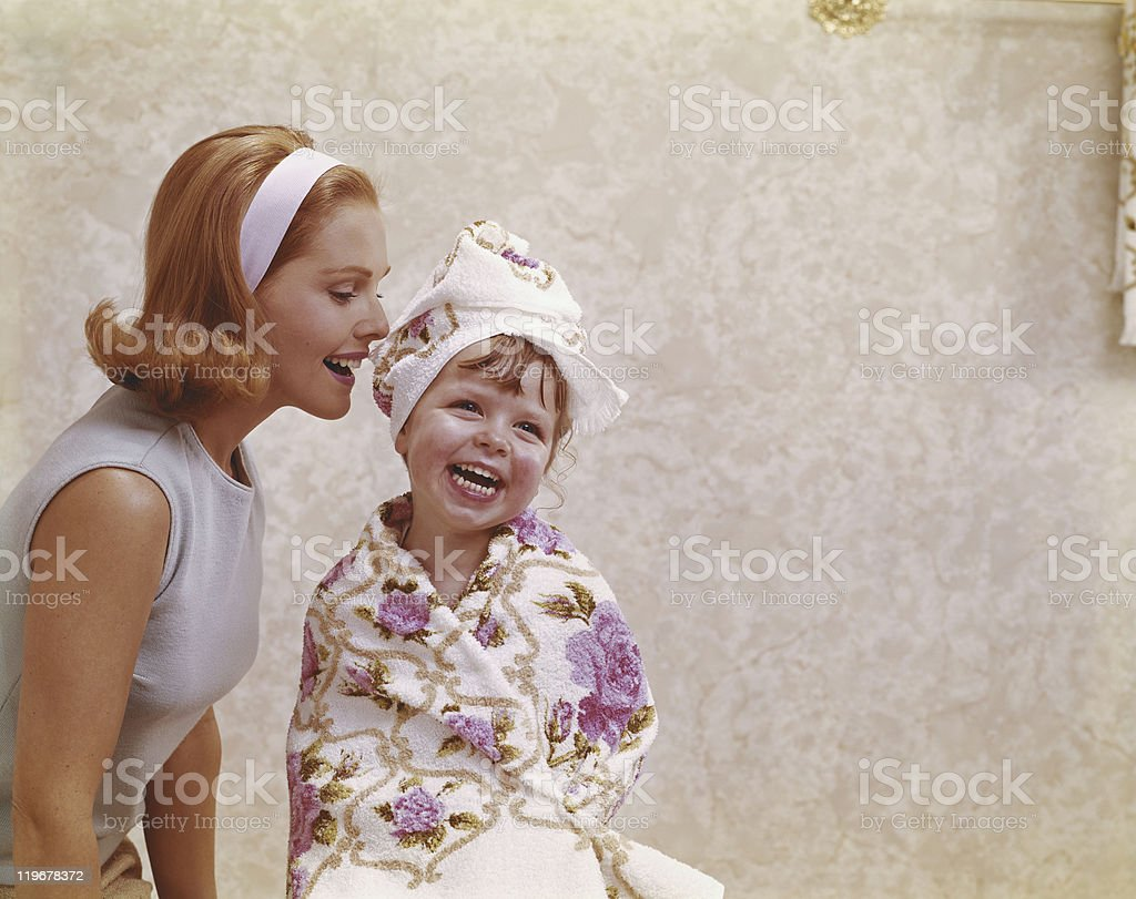 Mother whispering into her daughter ear, smiling stock photo
