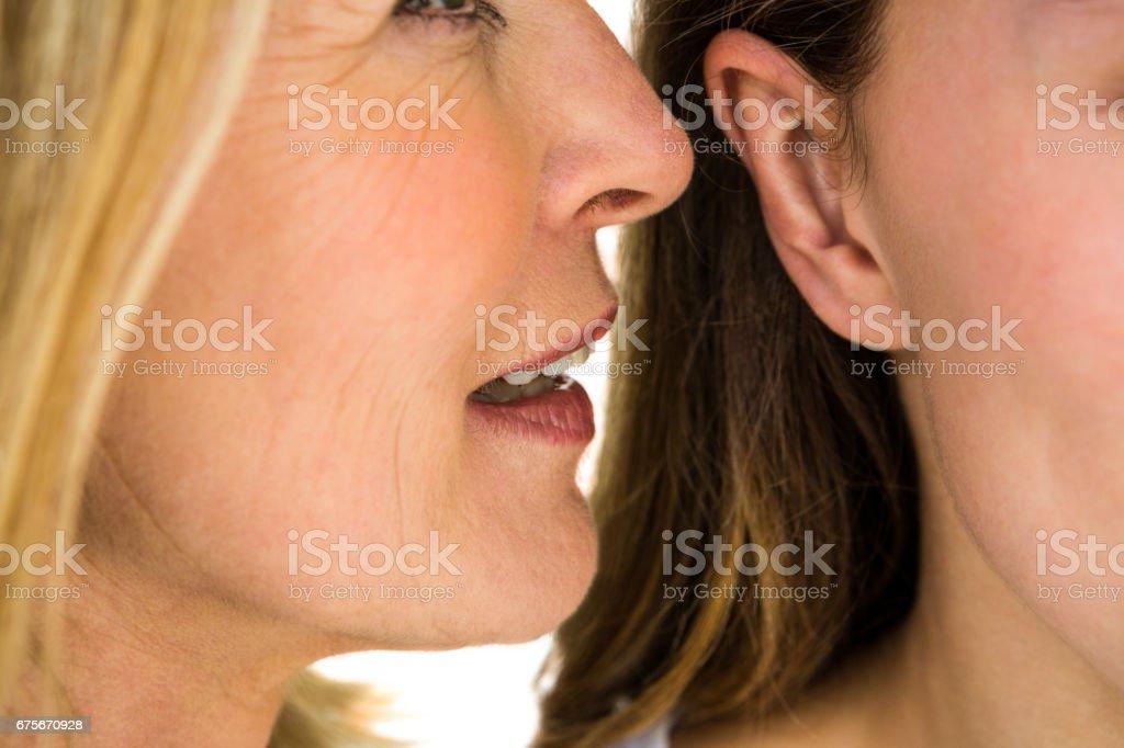 mother whispering something stock photo