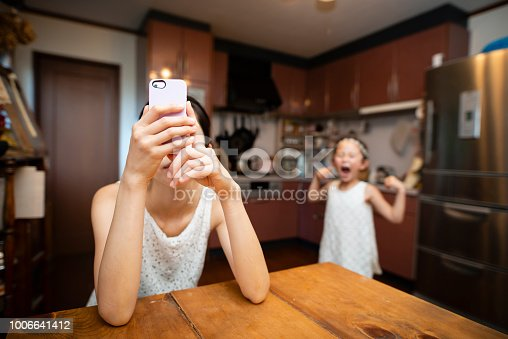 istock Mother who operates smartphone and angry daughter 1006641412