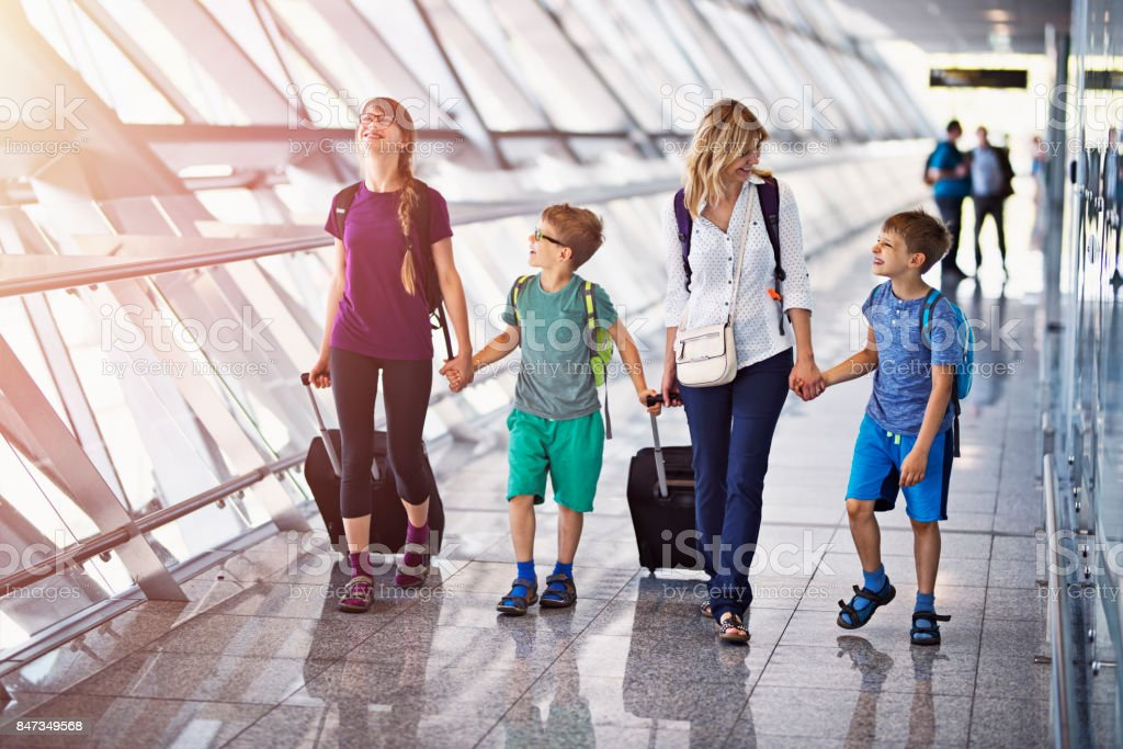 Mother with 3 kids walking in the airport lobby stock photo