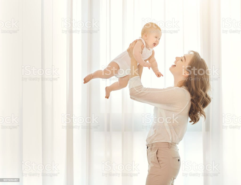 Mother with a baby in her arms plays against the window stock photo