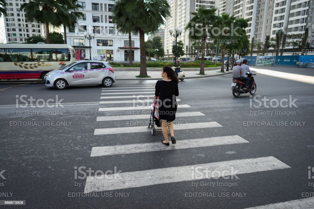 Hanoi, Vietnam - Oct 19, 2016: Mother with a baby stroller crossing the street in Minh Khai. Vehicles running on street stock photo