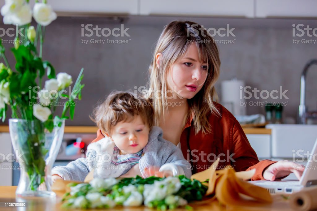 Mother with a child trying to working as a florist businesswoman stock photo