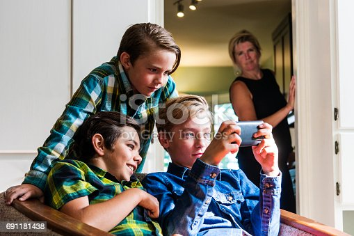A mother looks on from the kitchen as two pre-teen boys use a smartphone in the living room.  She is out of focus but it is clear to see her looking on with curiosity at what they are doing on line.