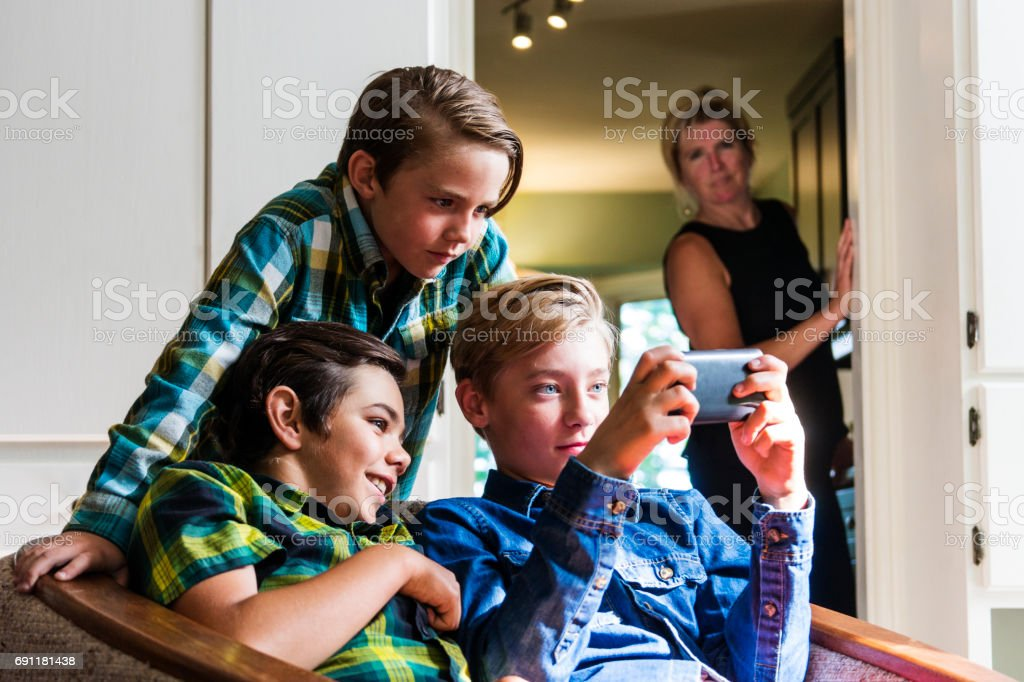 Mother with a neutral not unhappy look on her face watching boys using the internet on a phone stock photo